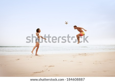 Young multicultural couple playing football on beach - stock photo