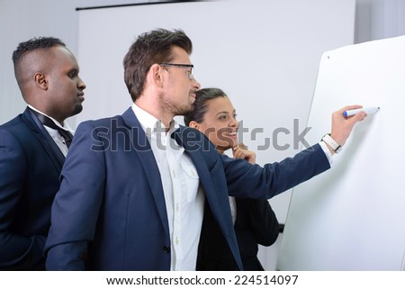 Young multiethnic business team planning a new strategy standing grouped in front of a flip chart analyzing a chart - stock photo