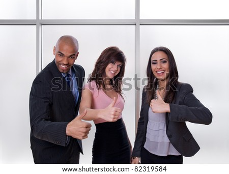 Young multiethnic business team smiling and showing thumbs up. - stock photo