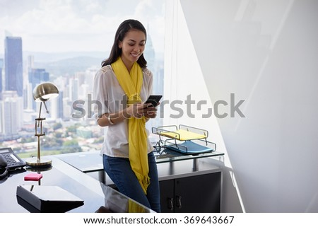 Young multiethnic Chinese Hispanic woman leaning on table in a modern office building, with sight of the city in background. She holds a mobile phone and smiles happy - stock photo