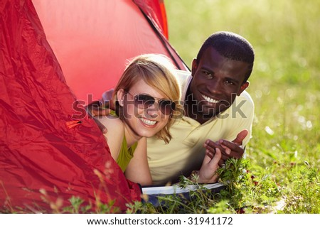 young multiethnic couple lying in tent and holding hands. - stock photo