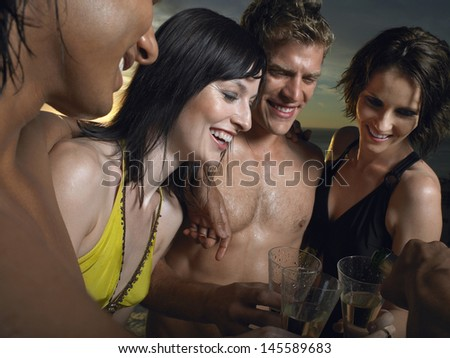 Young multiethnic people in bathing suits toasting champagne outdoors - stock photo