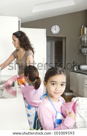 Young mum and daughter washing up and drying dishes in a home kitchen. - stock photo