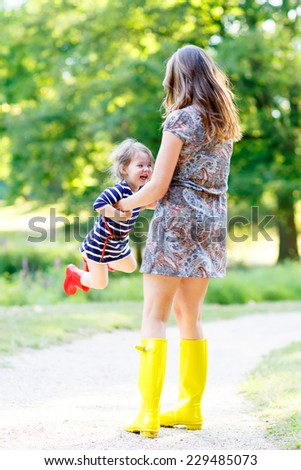 Young mum and little daughter in rubber boots having fun together, family look, in summer park on sunny warm day. Long legs of woman. - stock photo