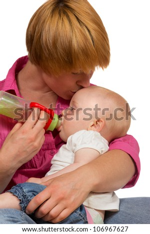 Young Mum bottlefeeding her adorable small baby cradled in her arms as she kisses it lovingly on the forehead - stock photo