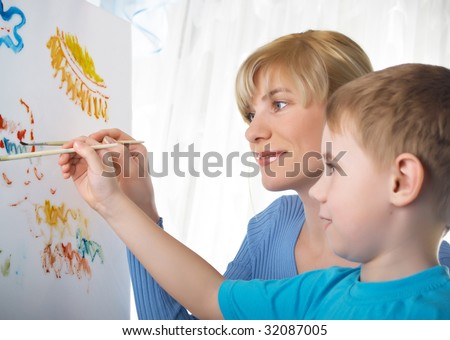 Young mum draws with the son paints - stock photo
