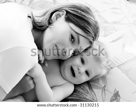 Young mum is played with the small son - stock photo