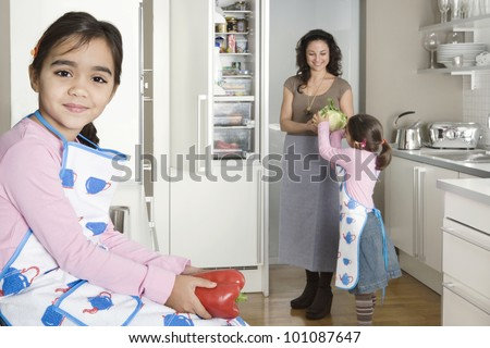 Young mum taking vegetables out of the fridge in a home kitchen with twin daughters. - stock photo