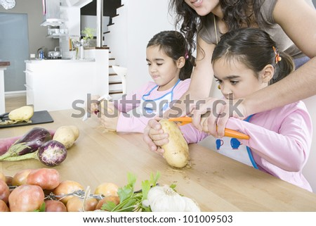 Young mum teaching twin daughters how to peel potatoes. - stock photo