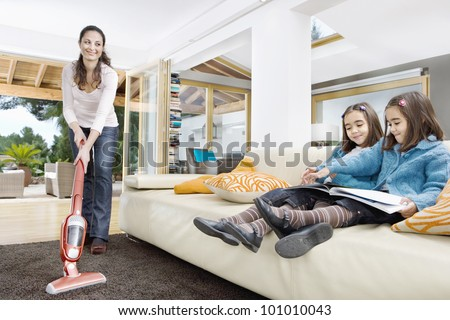 Young mum using a vacuum cleaner while her two twin daughters look at a book in the living room. - stock photo