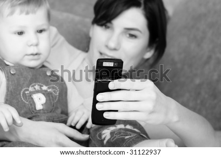 Young mum with the small beautiful boy together look at a mobile phone - stock photo