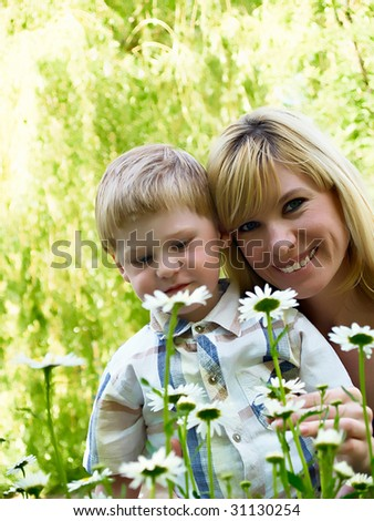 Young mum with the son on a floor from colors - stock photo