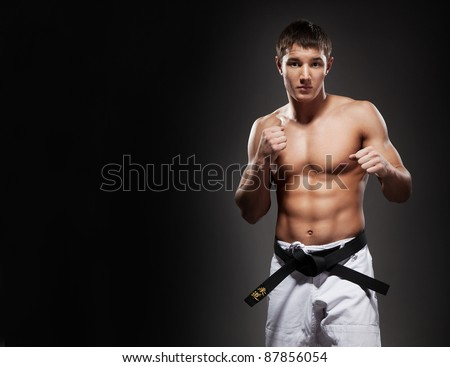 Young muscle karate sportsman pose on black background - stock photo