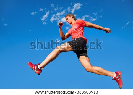 young muscular athlete is running   background of blue sky - stock photo