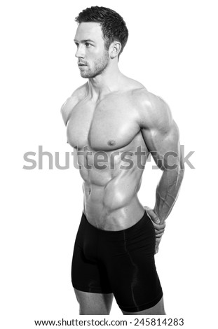 young muscular bodybuilder showing of his fit body. Shirtless with abs isolated on white background - stock photo