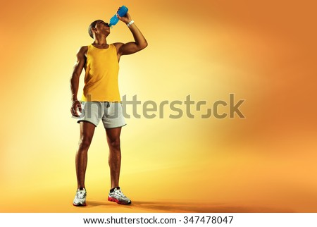Young muscular build man drinking water of bottle after running, attractive athlete resting after workout outdoors, fitness and healthy lifestyle concept. Isolated on yellow - stock photo