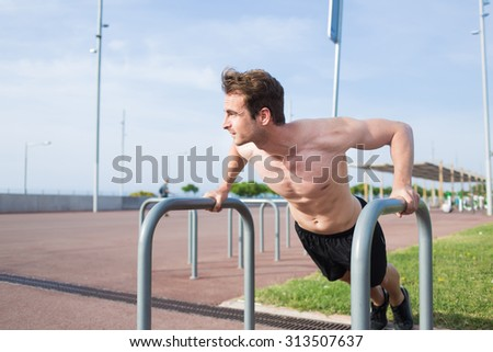 Young muscular build man shirtless doing push-ups exercise outworn on iron pipes gym equipment, handsome male runner warming up before began his morning workout training - stock photo