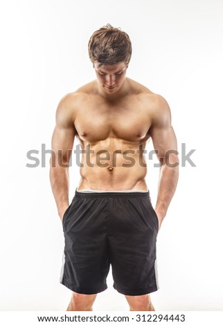 Young muscular guy in black shorts isolated on white background. - stock photo