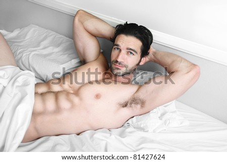 Young muscular male model lying back in bed with sexy smile - stock photo