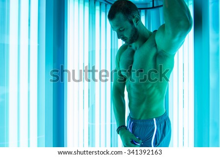 Young Muscular Man At Solarium In Beauty Salon - stock photo