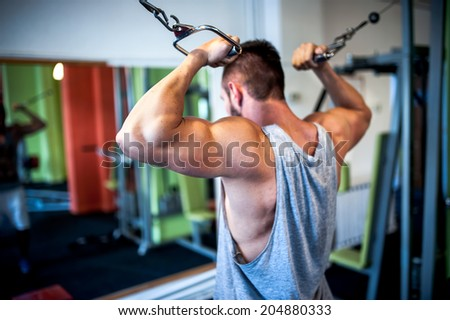 young, muscular man, bodybuilder working out in gym. Fitness concept on healthy life, sports and gym - stock photo