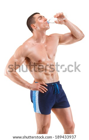 Young muscular man drinking water, isolated on white background - stock photo
