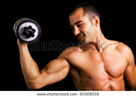 Young muscular man lifting dumbbells against black background - stock photo