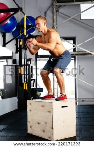 Young muscular man perfecting the box jump. Crossfit training - stock photo