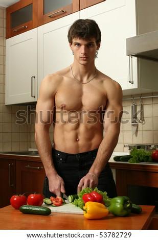 Young muscular man preparing salad at the kitchen - stock photo
