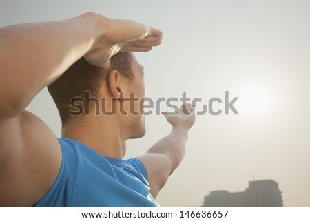 Young Muscular Man Stretching Toward the Sun - stock photo