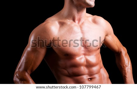 Young muscular man with beautiful torso agaisnt black background - stock photo
