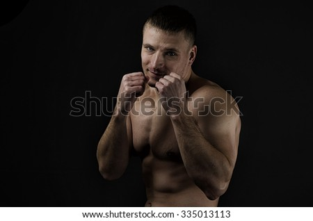 Young muscular man with boxing defensive stance against a black background. Hard light, dark lighting - stock photo