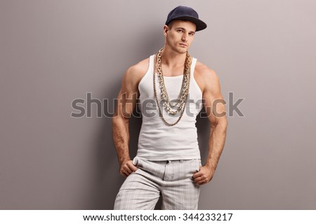 Young muscular rapper with a gold chain leaning against a gray wall and looking at the camera - stock photo