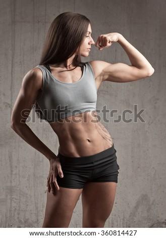 Young muscular sportswoman show biceps near stone wall - stock photo