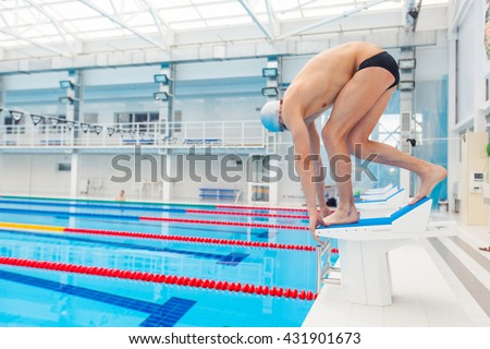 Young muscular swimmer in low position on starting block a swimming pool - stock photo