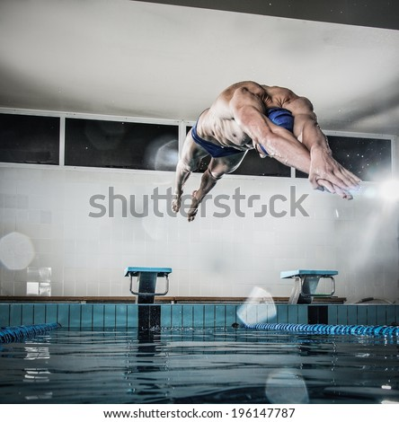 Young muscular swimmer jumping from starting block in a swimming pool - stock photo