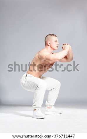 young muscular white man doing squats on gray background - stock photo