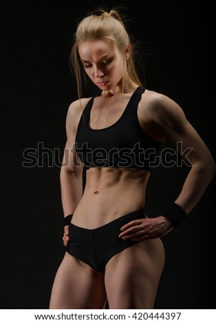 Young muscular woman posing on black background - stock photo