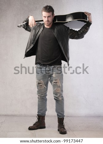Young musician holding a guitar on his shoulders - stock photo