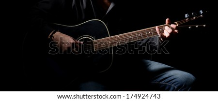 Young musician playing acoustic guitar and singing, on dark background - stock photo
