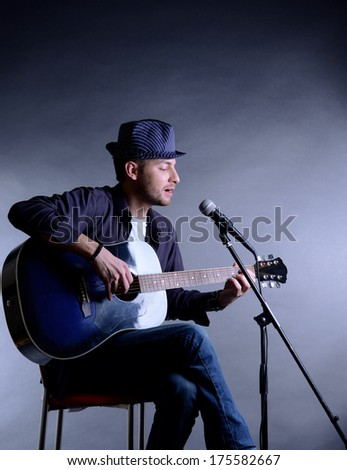 Young musician playing acoustic guitar and singing, on gray background - stock photo