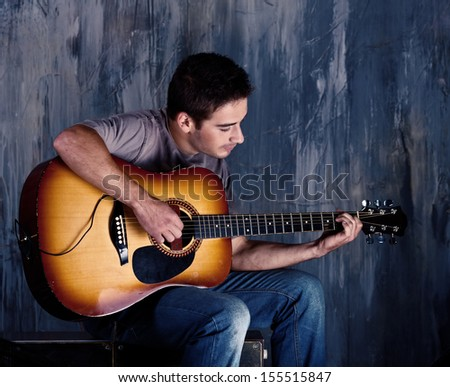 young musician playing the guitar - stock photo