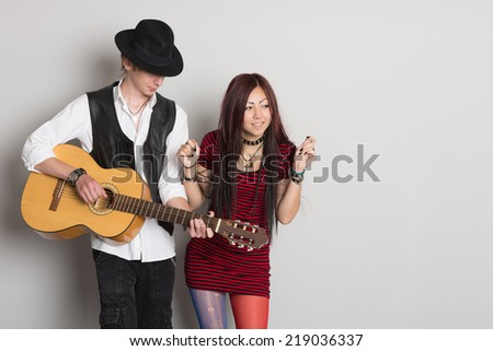 Young musicians play the guitar and dance. Asian woman and Caucasian man.   - stock photo