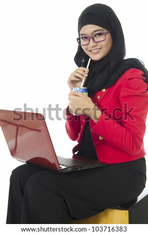 Young Muslim girl sitting with notebook while drinking over white background. - stock photo