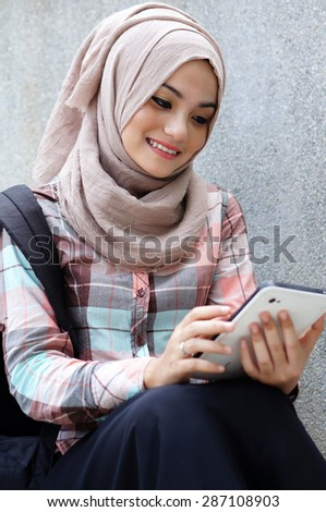 Young muslim girl student using her tablet. - stock photo