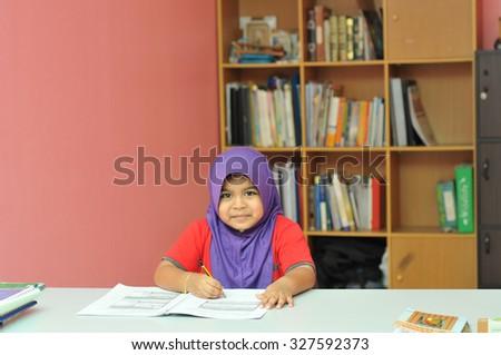Young Muslim girl studying - stock photo