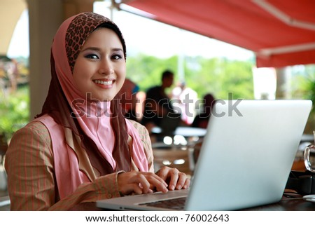Young Muslim Girl using laptop and smile to the camera - stock photo