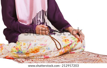 Young muslim girl with rosary praying on white background - stock photo