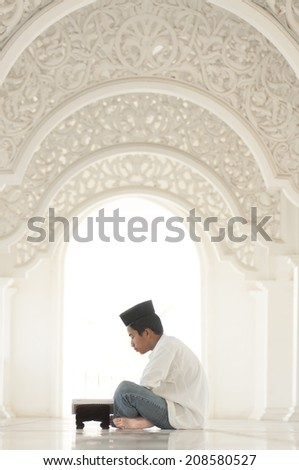 Young Muslim Man Reading The Quran - stock photo