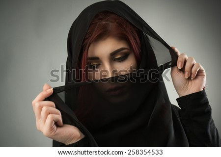 Young muslim woman covering her hair and face with a black veil - stock photo